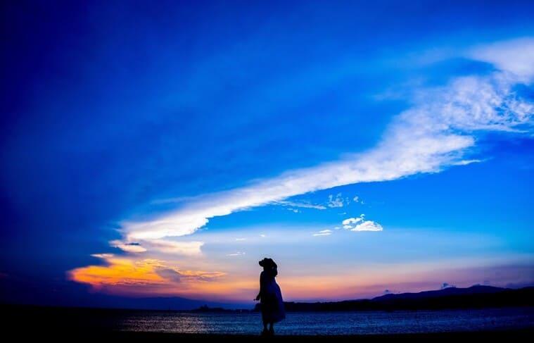 海岸を歩く女性のシルエット