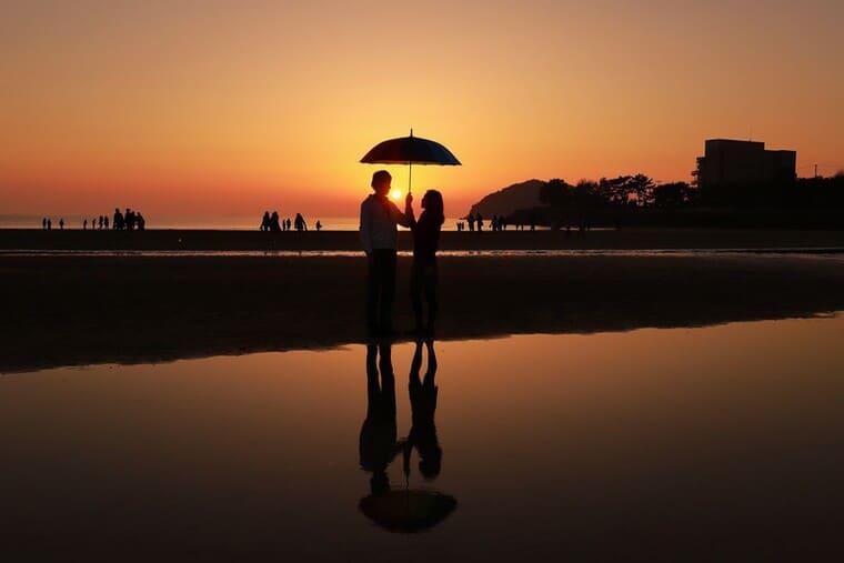 夕暮れの浜辺で相合傘をするカップル