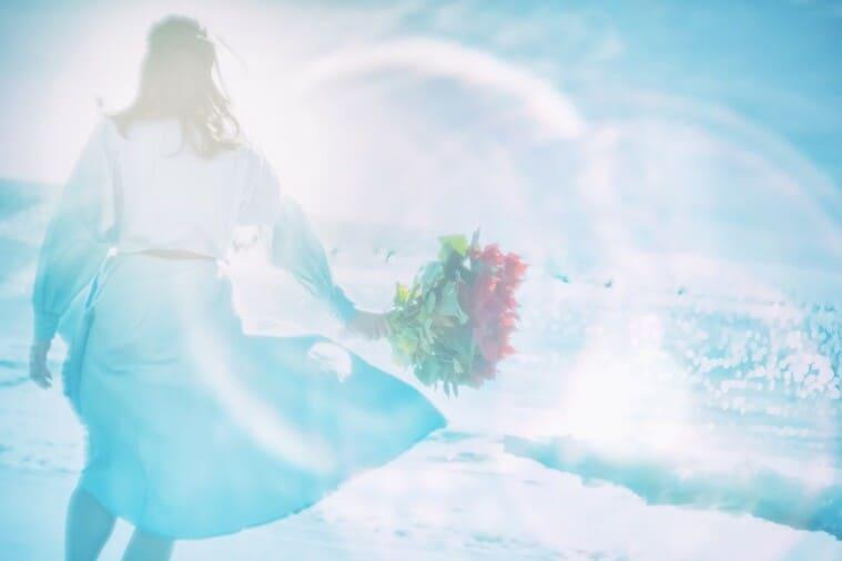 海辺で花束を持つ女性のフォトモンタージュ