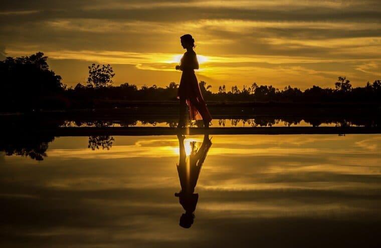 日の出のビーチにいる女の子のシルエット